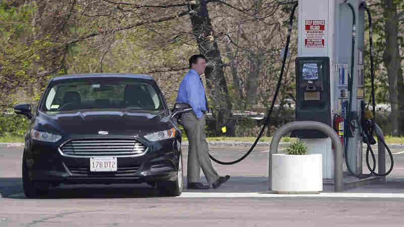 A customer fuels his car at a gas station in Pembroke, Mass. Economists say Americans have been slow to spend the money they saved from lower energy prices.
