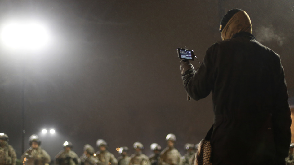 A protester films National Guard troops Nov. 26 in front of the Ferguson Police Department in Ferguson, Mo.