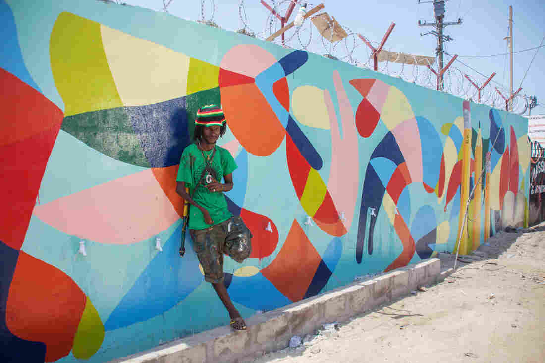 Guinean artist Kingston Sylla and Nanook spent days painting in the details of an abstract mural that brightens up the concrete wall in front of the school. It was his idea to add pencils to the design.
