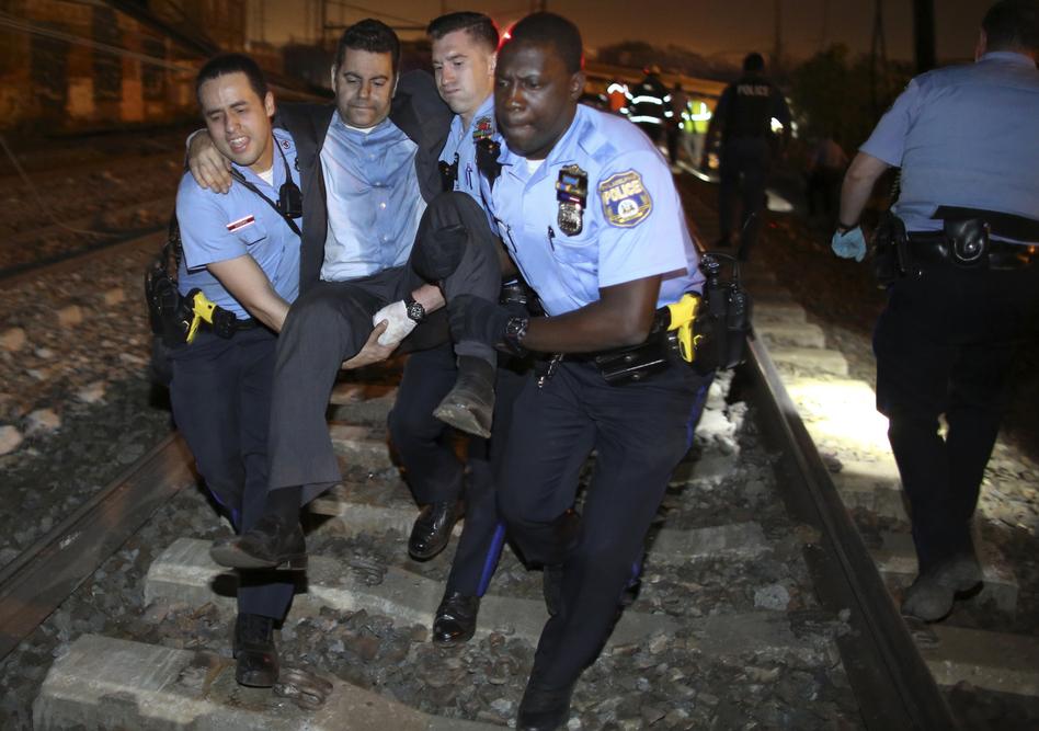 Emergency personnel help a passenger at the scene of a train wreck, Tuesday, in Philadelphia. (Joseph Kaczmarek/AP)