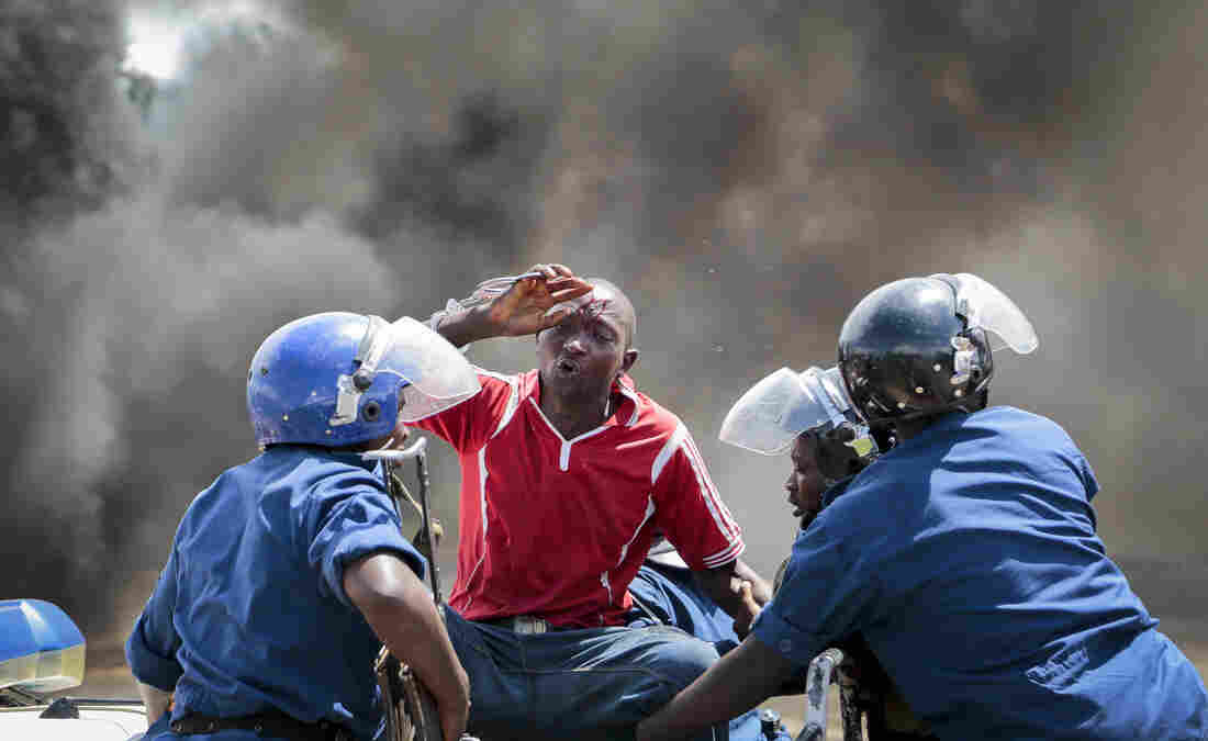 A wounded protester is detained by police as demonstrators try to march to the town center of Bujumbura, Burundi, on Wednesday.