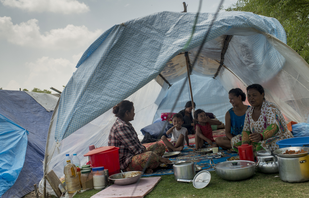 A family sits inside a tent at Kathmandu's golf course Wednesday, a day after a strong earthquake hit the area.