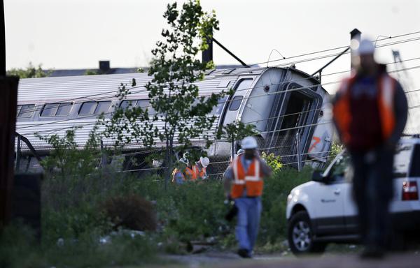 Emergency personnel walk near the scene of a deadly train wreck on Wednesday in Philadelphia.