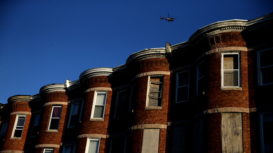 """A helicopter flies over a section of Baltimore affected by riots. Richard Rothstein writes that recent unrest in Baltimore is the legacy of a century of federal, state and local policies designed to """"quarantine Baltimore's black population in isolated slums."""" (Patrick Smith/Getty Images)"""