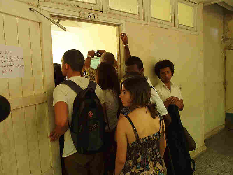 Students at the Escuela Nacional de Arte in Havana huddle around a doorway during a master class given by members of the visiting Minnesota Orchestra.