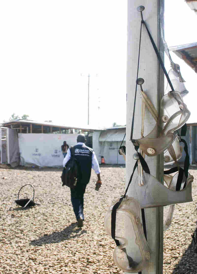 Dr. Michael Mawanda, from the World Health Organization, walks past goggles left to dry during the last days of operation at the Ministry of Defense ETU.