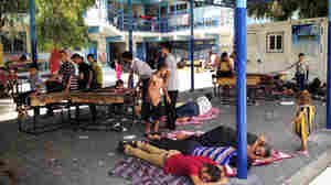 Displaced Palestinians seek shelter in the courtyard of a United Nations-run elementary school in Jabaliya, a northern Gaza town, in July 2014 — shortly before the school was hit by what the UN says was Israeli artillery. Israel has opened a criminal investigation into the attack.