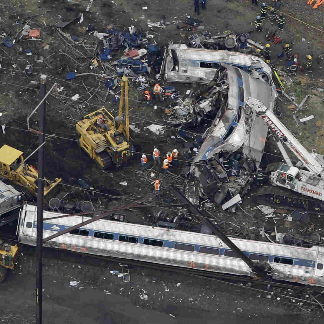 Emergency personnel work at the scene of a deadly train wreck, on Wednesday. The FBI is now looking into the possibility that the locomotive was struck by some sort of projectile.