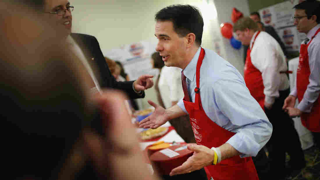 Wisconsin Gov. Scott Walker offers cheese and ice cream to guests in his hospitality room at the Iowa Lincoln Day Dinner in Des Moines on Saturday.