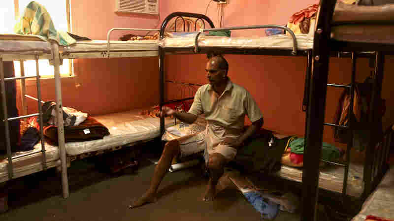 In this photo taken May 3 during a government-organized media tour, Kuttamon Chembadnan Velayi from Kerala, India, speaks to journalists while sitting on his bed in a room he shares with seven other Indian laborers in Doha, Qatar. The housing facility has been cited by Qatari labor officials for substandard conditions.