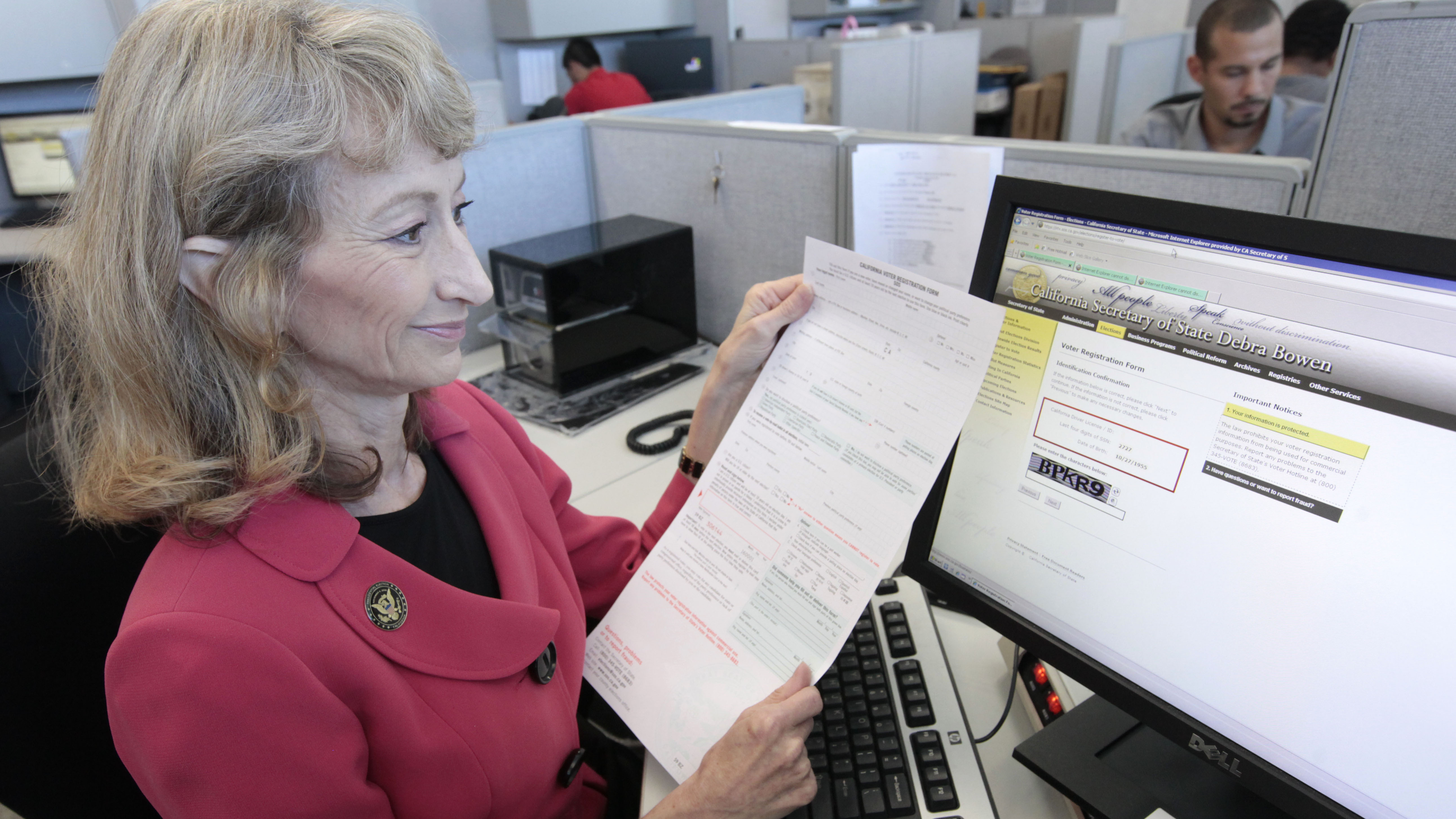 Debra Bowen, then California secretary of state, demonstrates the state's online voter registration system when it was launched in 2012. Voters can also still register using a paper form.