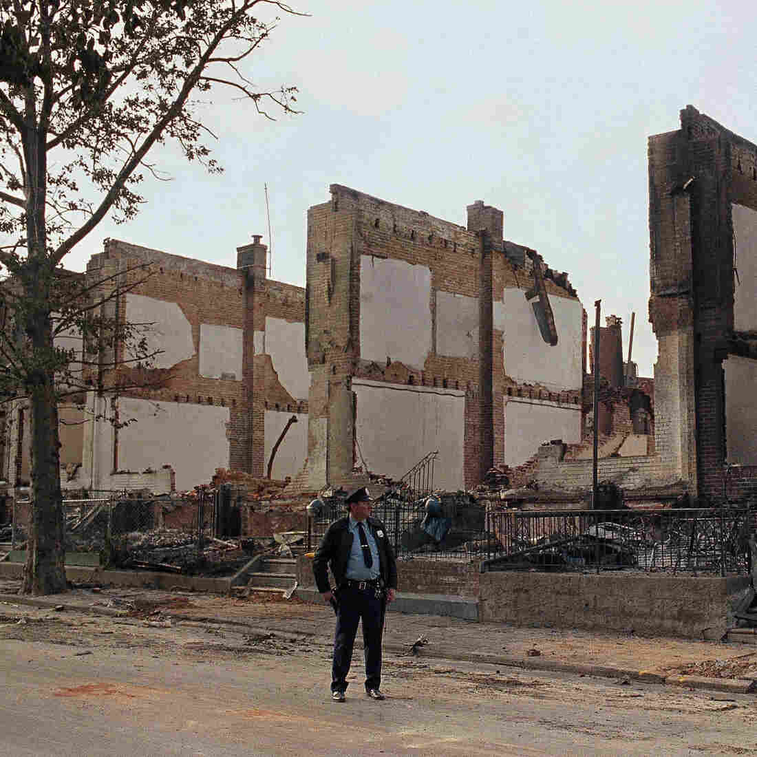 A policeman stands guard on Pine Street in West Philadelphia near the remains of 61 row houses days after they were destroyed by fire on May 13, 1985, when police dropped explosives into a house occupied by members of the radical group MOVE.