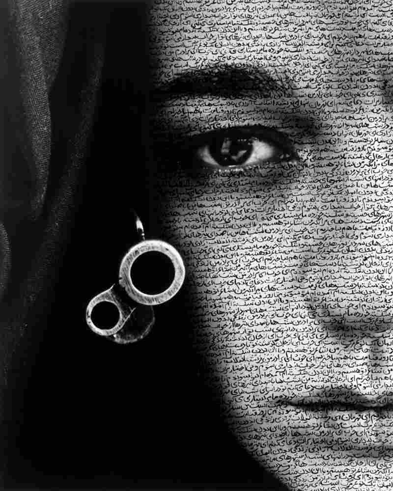 Calligraphy is often layered on the people in Neshat's photos. It falls over them like veils, or tattoos their skin. Curator Melissa Ho says text gives these silent faces a voice. Above, Neshat's 1996 work Speechless from the Women of Allah series.