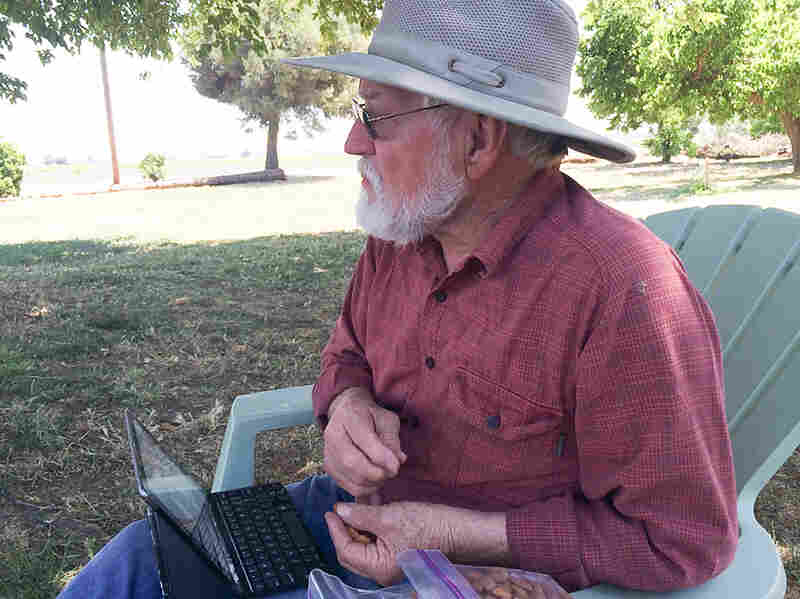 "Glenn Anderson snacks on almonds at his farm in Hilmar, Calif. He's not a fan of pasteurizing the nuts — he says it ruins the taste, so that it ""leans towards cardboard, as opposed to fresh almonds."""
