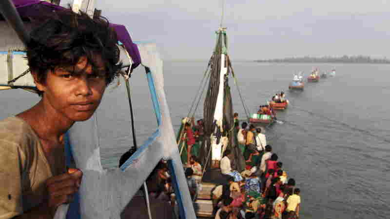 A fishing boat carrying Rohingya and Bangladeshi migrants is pulled to sho