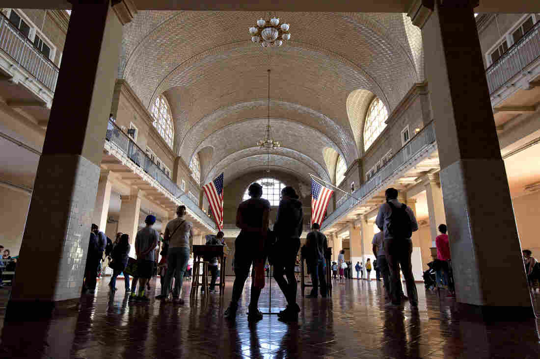 Tourists meander through the Great Hall in the Ellis Island National Immigration Museum. A new exhibition at the museum tells stories of immigrants who have come as recently as the start of this century.