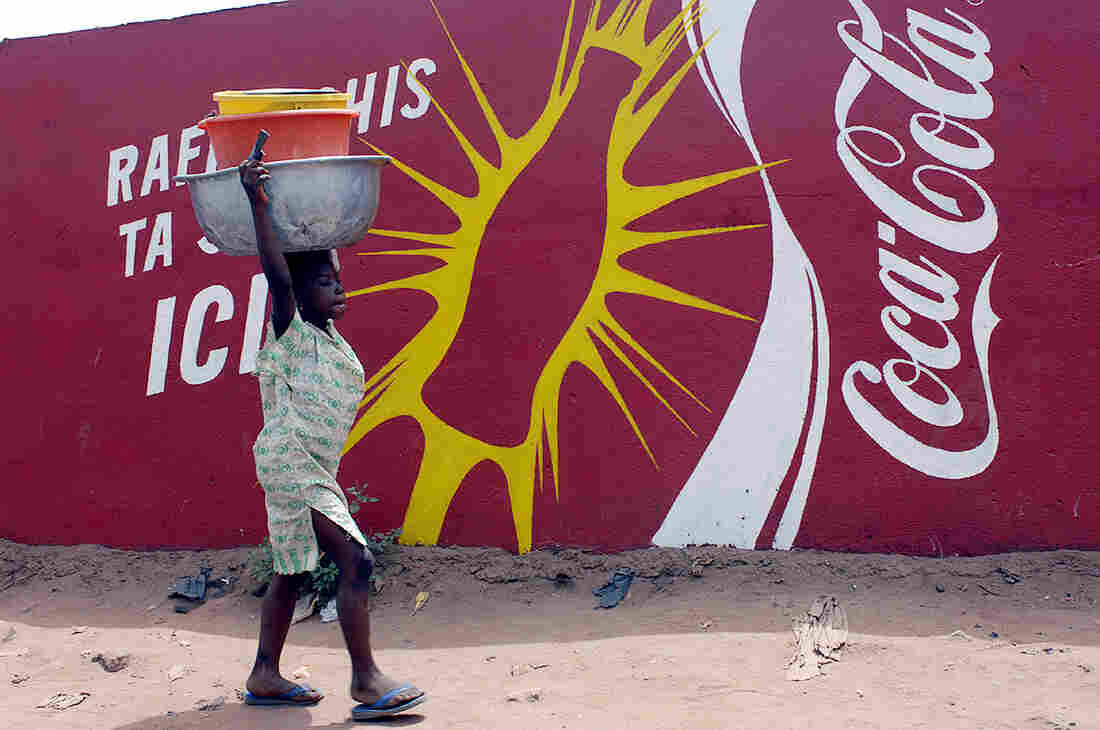 A woman walks past an ad for Coca-Cola in Bamako, the capital of the Republic of Mali.