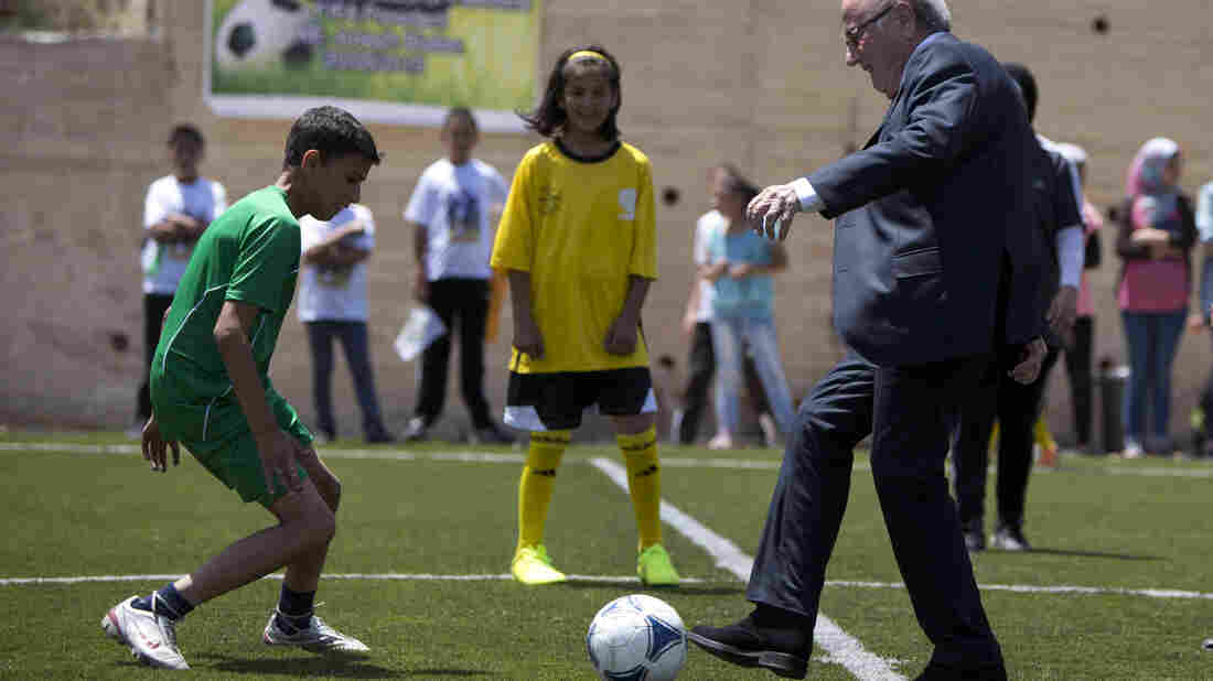 """FIFA President Sepp Blatter kicks a ball during the inauguration of a football stadium in the village of Dura al-Qari near the West Bank city of Ramallah on Wednesday. Blatter said he is on a """"mission of peace"""" to resolve tensions between the Israeli and Palestinian soccer federations."""