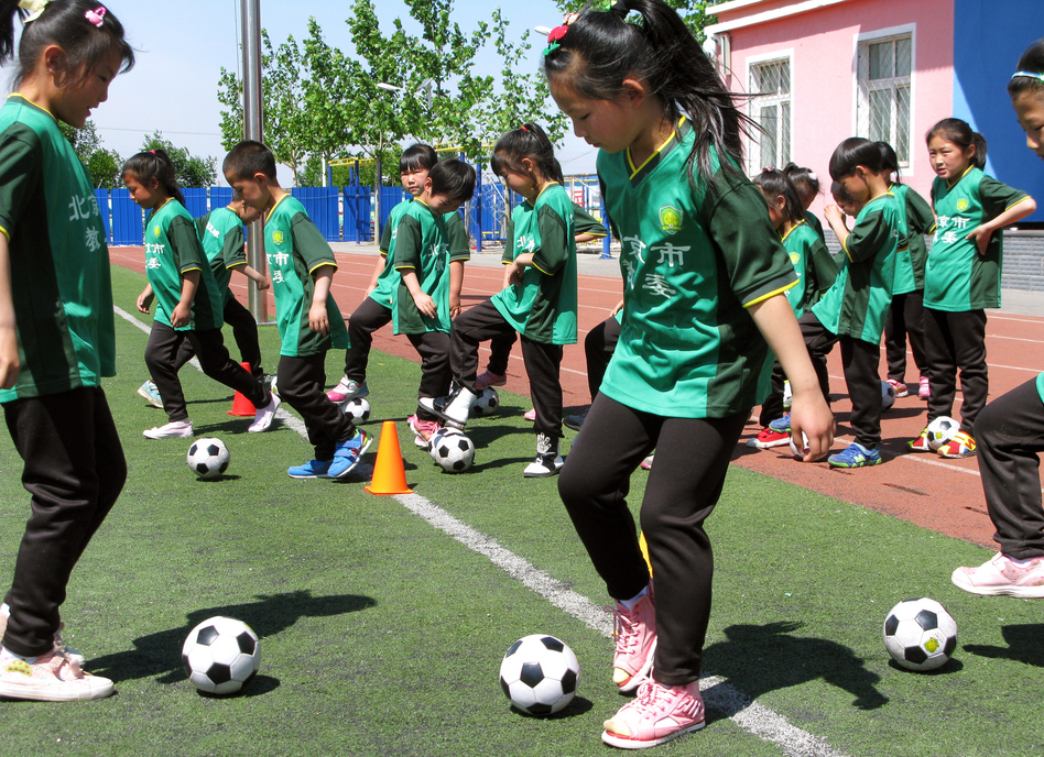 First-graders take soccer class at the Nandulehe Elementary School in suburban Beijing. The school is one of 20,000 that's launching a national soccer curriculum in the next five years. It's part of a government plan to raise China's soccer skills and eventually, China's leaders hope, host and win a World Cup. (Anthony Kuhn/NPR)