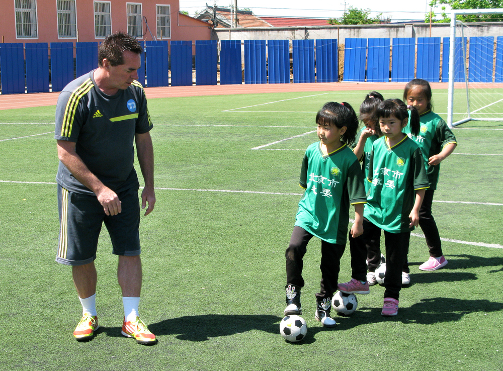American Tom Byer, a former professional soccer player now based in Tokyo, coaches first-grade students at the Nandulehe Elementary School in suburban Beijing. Byer is advising China's government in implementing an ambitious plan to upgrade the country's soccer programs.