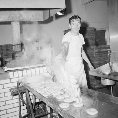 Steaming-hot bagels are scooped out of the water in which they were boiled and dumped onto a stainless steel drain board at a bagel bakery in Queens, New York City, 1963. Traditionally, bagels were boiled, but bakers who use the modern method skip this step.