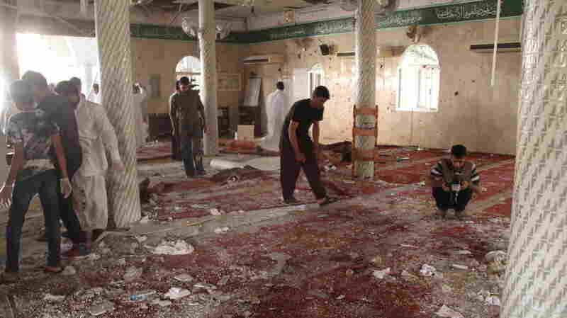 People examine the debris following a suicide bomb attack Friday at the Imam Ali mosque in the eastern village of al-Qadeeh in Saudi Arabia's Gatif province. A branch of the self-declared Islamic State has claimed responsibility for the attack.