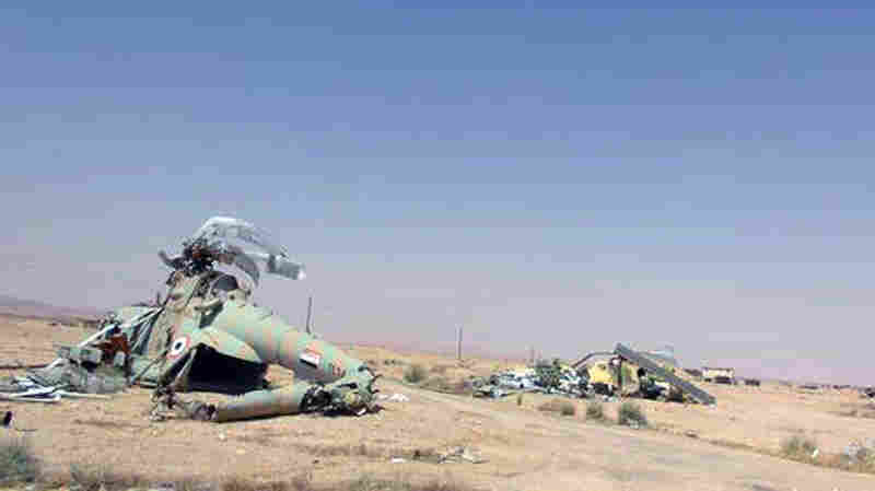 In this photo released Thursday by a website run by Islamic State militants, damaged Syrian helicopters sit at Palmyra air base, which was captured by ISIS after a battle with the Syrian government forces earlier this week.
