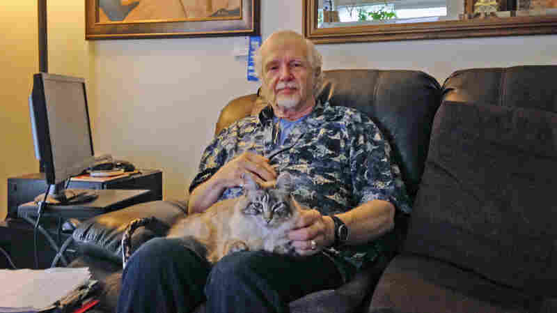 Retired California school teacher Mikkel Lawrence sits with his cat, Max. Lawrence has hepatitis C and has struggled to afford the medicine he needs to treat it.