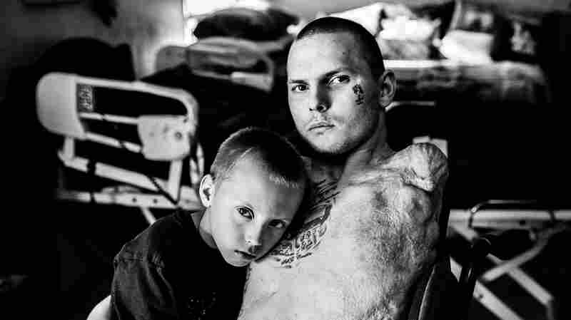 Army Spc. Jerral Hancock sits for a portrait with his son Julius. It is believed that Hancock was trapped under the wreckage of his Army tank for half an hour before he was rescued.