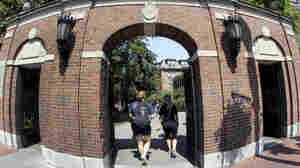 Students walk through a gate on the Harvard University campus. In a recent complaint, dozens of groups have alleged that the school's admissions process holds Asian-American applicants to an unfairly high standard.