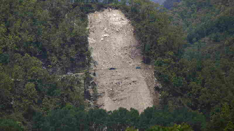 Vehicles pass by a landslide area after the earthquake in Gorkha district last week. A fresh landslide in the same area has cut off a major river, threatening villages downstream.