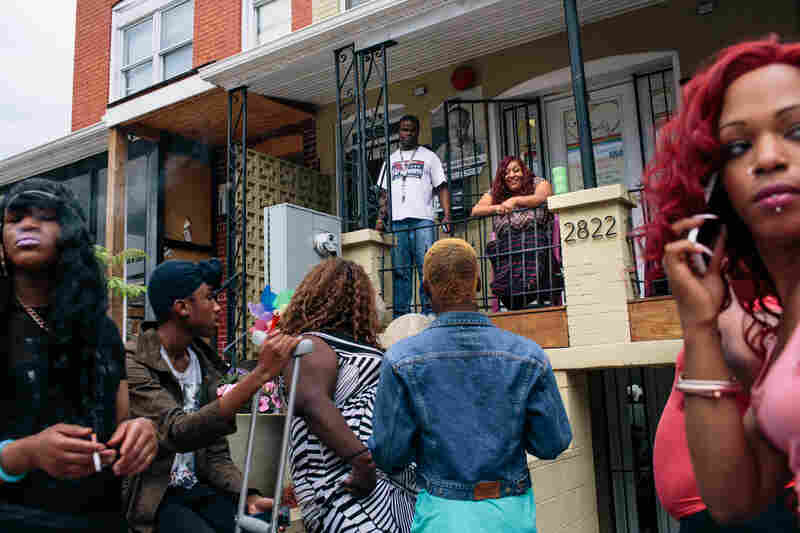 Ruby Corado (top center) sits on the porch of Casa Ruby, a drop-in and service center for transgender people in Washington, D.C., while many of her clients, friends and employees hang out in front.