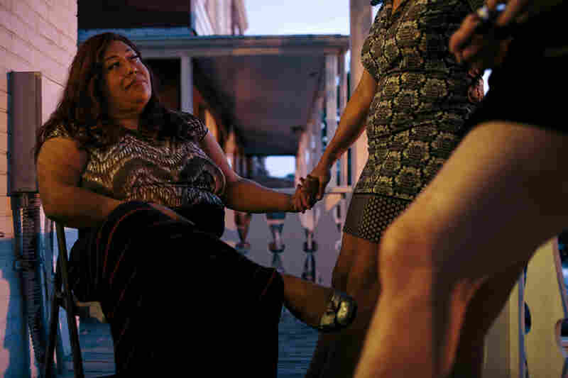 Ruby Corado (left) holds hands with her friend and Casa Ruby board member Consuella Lopez on the porch of one of the transitional group homes Corado runs in Washington, D.C.