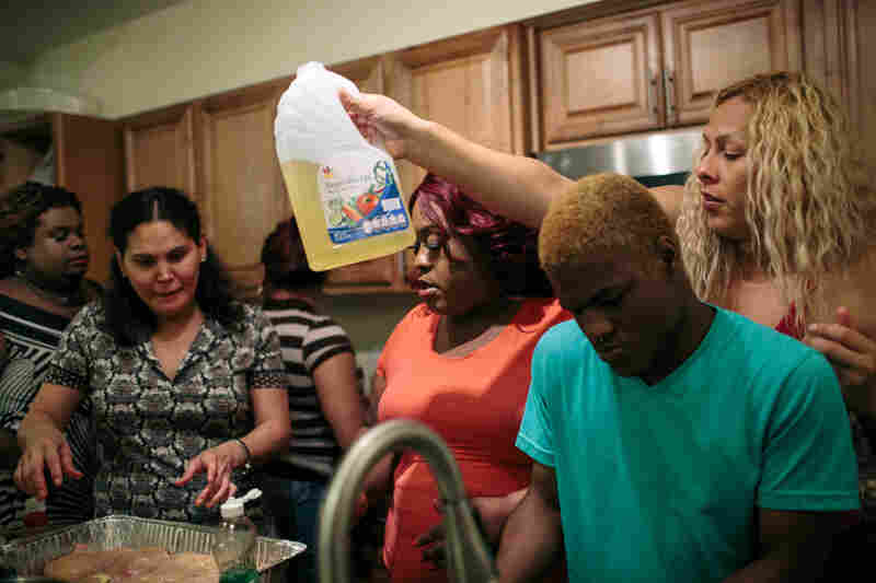 Lissa Alfaro (far right) squeezes between Lacyy Coates, 20, and Lazema Mills, 30, as they each help making dinner for a Cinco de Mayo party inside one of the group homes run by Ruby Corado.