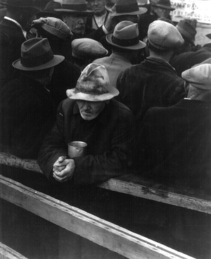 A man waits in a bread line in San Francisco during the winter of 1933.
