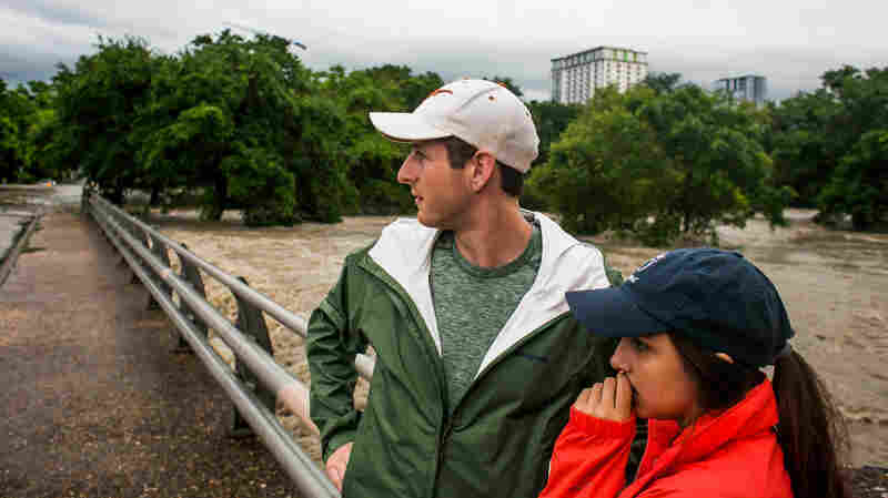 Forrest Huggleston and Alex Huff watch flooding at Shoal Creek after days of heavy rain in Austin, Texas, on Monday.