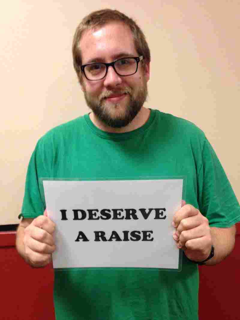 """Hall holding a sign that reads """"I deserve a raise"""" as part of a petition drive organized by his union."""
