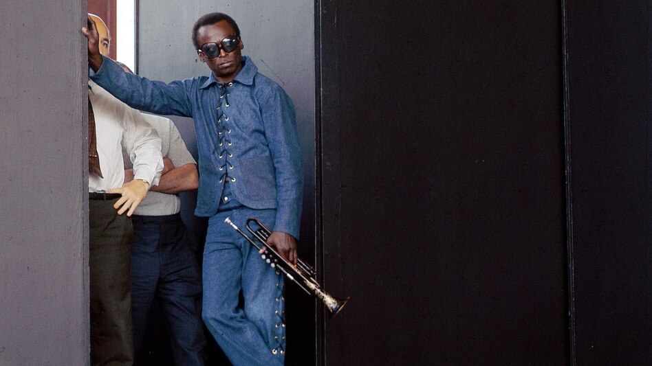 Miles Davis poses at the side of stage during the Newport Jazz Festival. (Redferns)