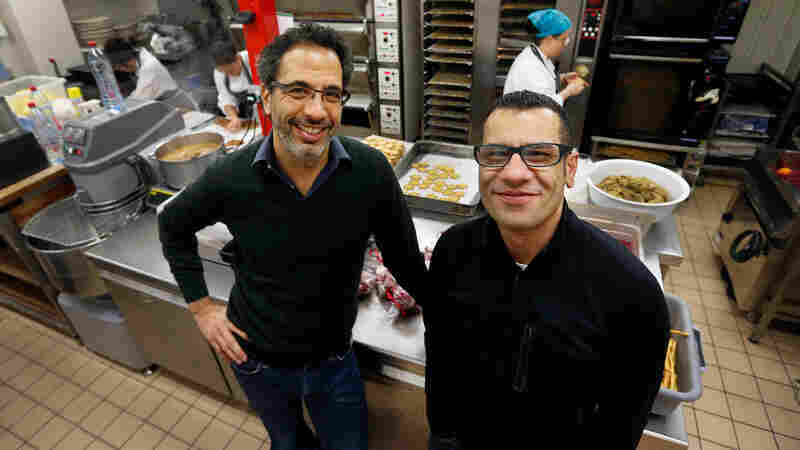 Chefs Yotam Ottolenghi (left) and Sami Tamimi pose for the photographer at their company's bakery in London, December 2012.