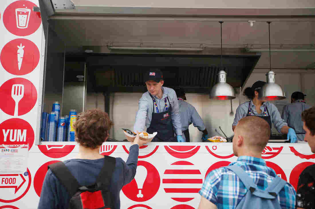 A man serves hamburgers at the USA Pavilion's food truck at Expo 2015 in Rho, near Milan, Italy. The Food Truck Nation exhibit highlights America's urban food truck trend.