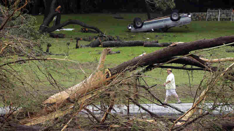 A man walks along a section of the Blanco River on Tuesday where sweeping floodwaters overturned vehicles and knocked down trees in Wimberley, Texas.