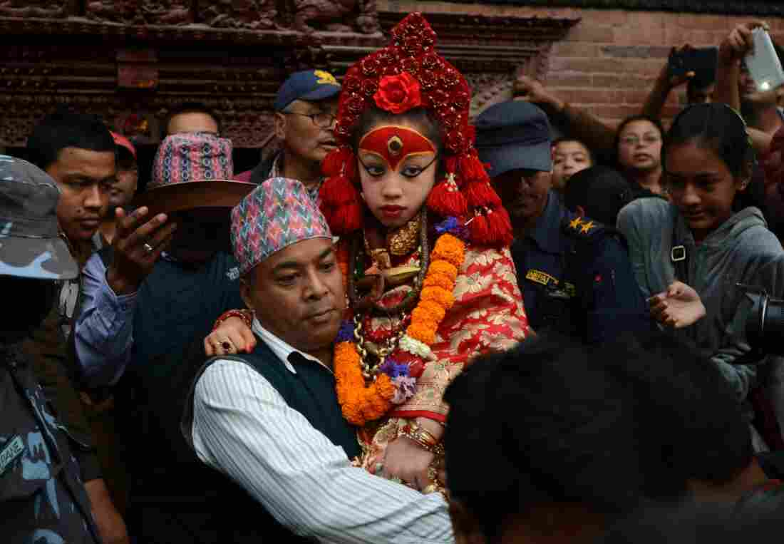 Nepal's Living Goddess, the Kumari Devi, 9, observes a chariot festival in Kathmandu on March 29. The goddess is worshipped by both Hindus and Buddhists. She's selected as a young child and lives an isolated and secretive existence and is rarely seen in public. Her historic home survived last month's earthquake with only minor cracks. She's being held by her caretaker Gautam Shakya.
