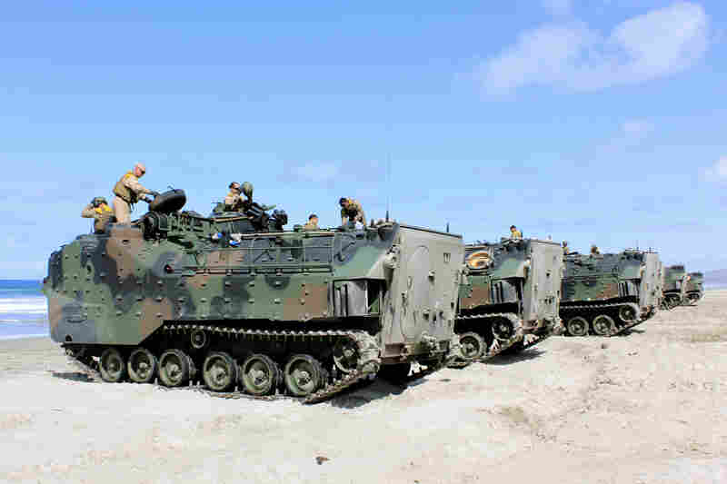 Amphibious assault vehicles, or AAVs, are lined up on the beach as they're prepared to be sent into the ocean for a training exercise.
