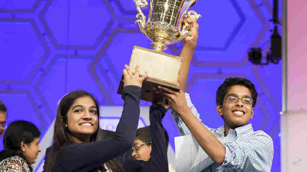 Vanya Shivashankar (left) of Olathe, Kan., and Gokul Venkatachalam of Chesterfield, Mo., lift the trophy after becoming co-champions Thursday night after the final round of the 88th annual Scripps National Spelling Bee at National Harbor in Maryland.