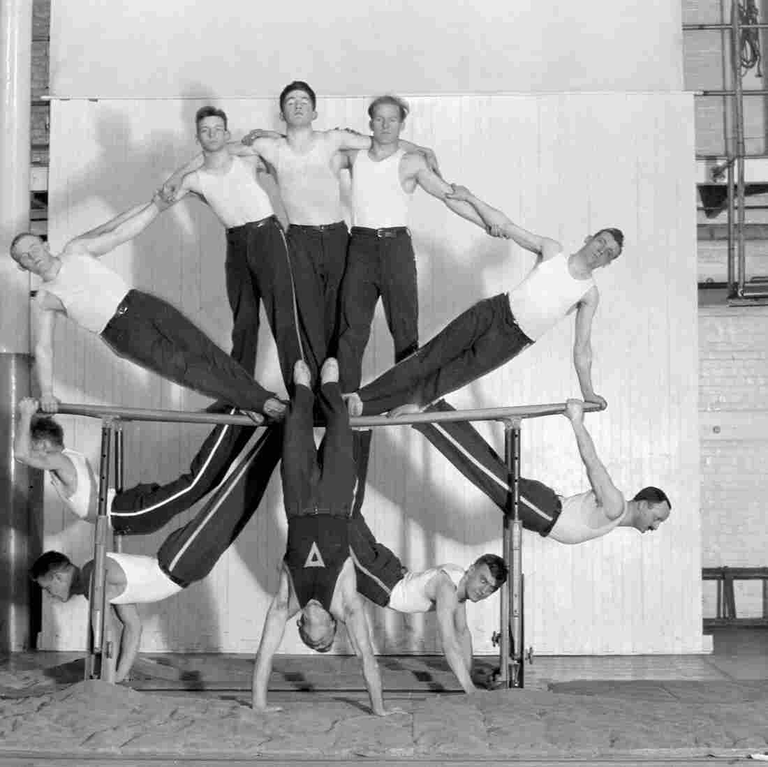 An adult gymnastics club performs a group stunt on the parallel bars at the Rochester, N.Y., YMCA at the beginning of the 20th century.