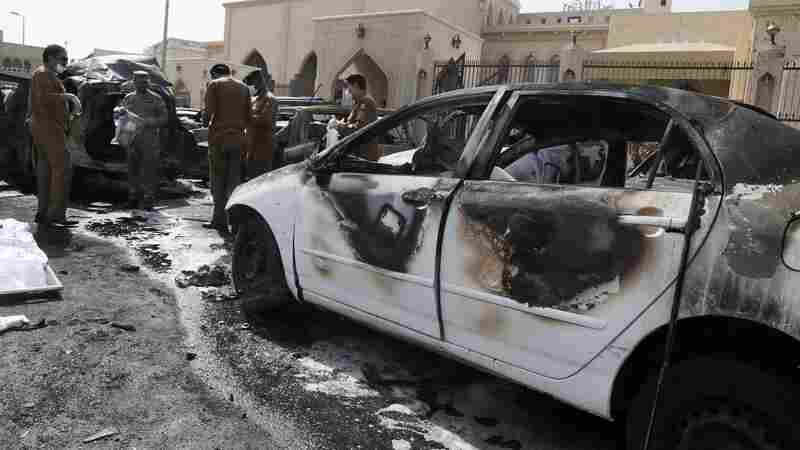 Members of the Saudi security services inspect the site of a car bomb attack targeting Shiite Saudis attending Friday prayers at a mosque in Dammam, Saudi Arabia.