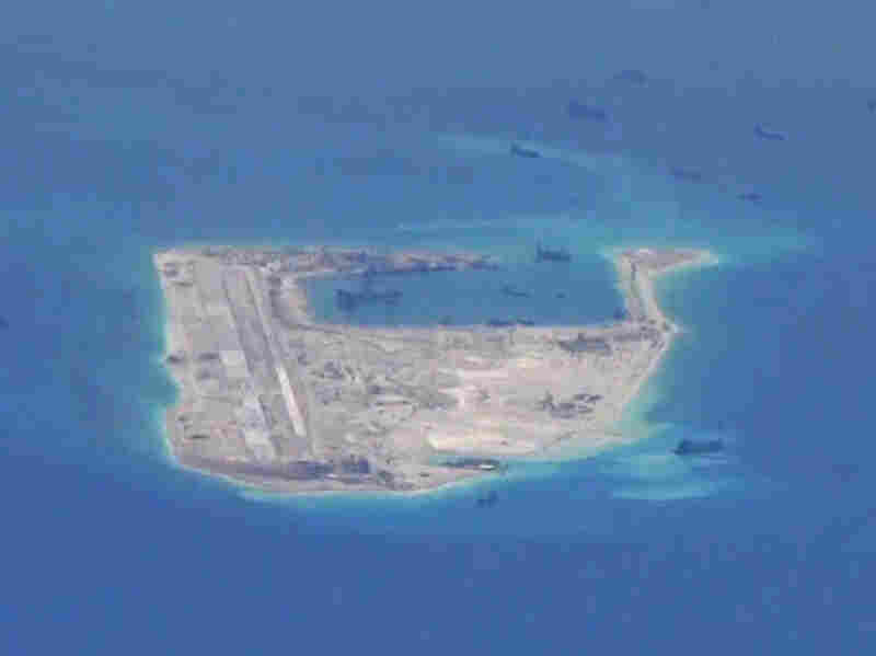 Chinese dredging vessels are purportedly seen in the waters around Fiery Cross Reef in the disputed Spratly Islands in this still image from video taken by a P-8A Poseidon surveillance aircraft provided by the U.S. Navy on May 21.