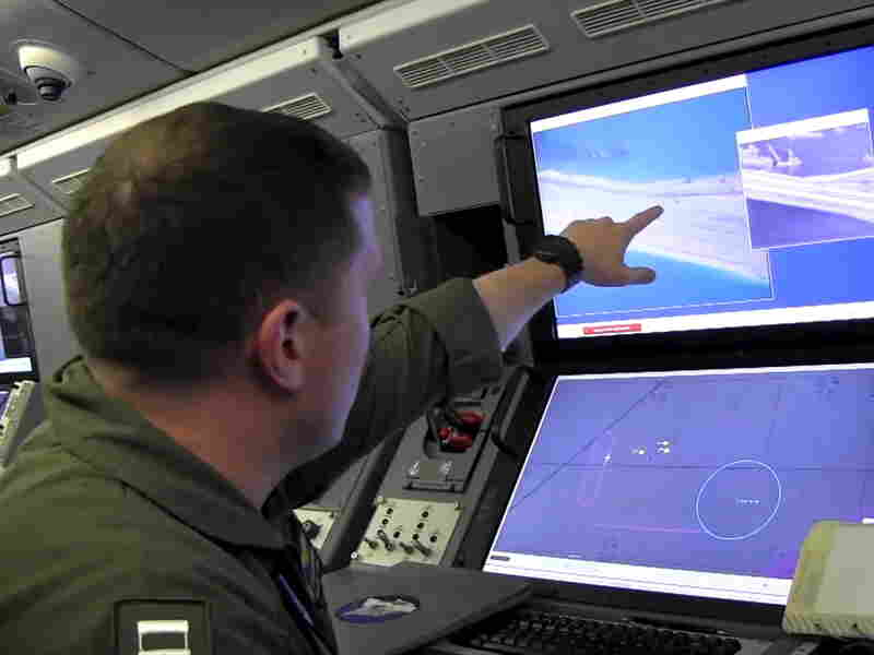 A U.S. Navy crewman aboard a P-8A Poseidon surveillance aircraft views a computer screen purportedly showing Chinese construction on the reclaimed land of Fiery Cross Reef in the South China Sea.