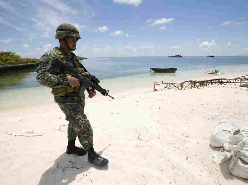 Filipino soldier Tychico Octobre patrols the shore of Pagasa Island during a visit by Gen. Gregorio Pio Catapang, the Philippines' military chief, on May 11.