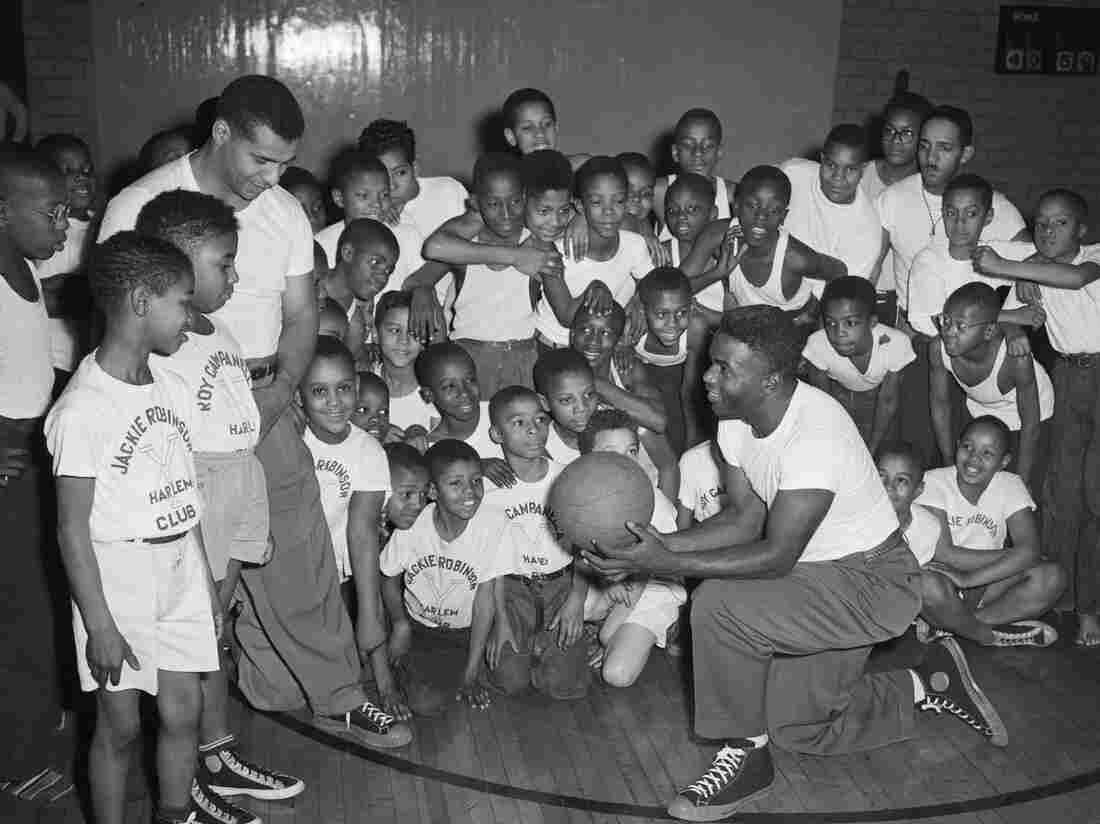 Baseball legends Jackie Robinson (kneeling) and Roy Campanella of the Brooklyn Dodgers teach basketball to a group of young boys at the YMCA in Harlem in 1948.